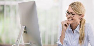 Femme souriante devant un ordinateur